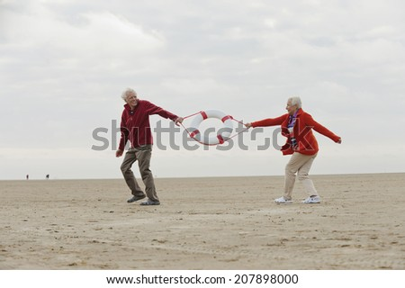 Germany, St Peter-Ording, North Sea senior couple pulling lifesaver on beach - stock photo