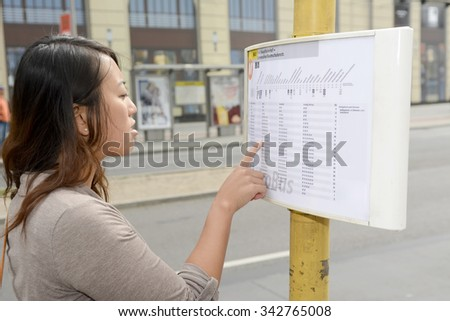 Germany, young woman reading timetable in Berlin - stock photo
