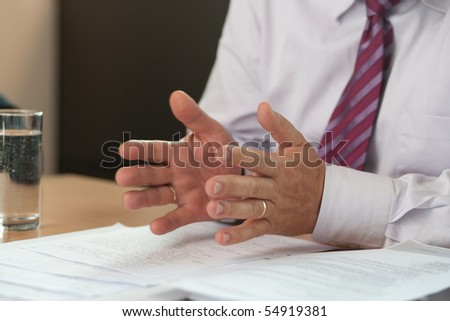 Gesticulating hands of a businessman at a meeting