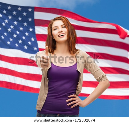 gesture and happy people concept - smiling girl in casual clothes showing thumbs up over american flag background