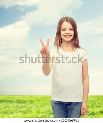 gesture and happy people concept - smiling little girl in white blank t-shirt showing peace gesture with fingers - stock photo