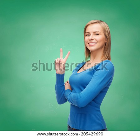 gesture and people concept - smiling teenage girl showing v-sign with hand - stock photo