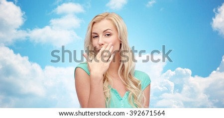 gesture and people concept - smiling young woman or teenage girl covering her mouth with hands over blue sky and clouds background - stock photo