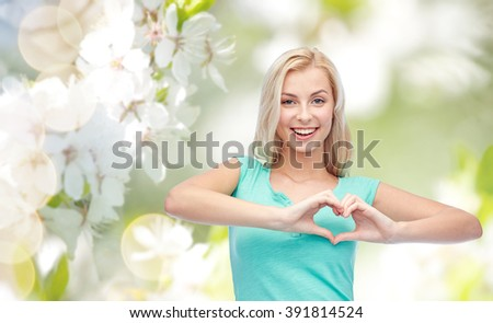 gesture and people concept - smiling young woman or teenage girl showing heart shape made of fingers over natural spring background - stock photo