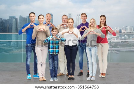 gesture, family, generation and people concept - group of smiling men, women and boy showing heart shape hand sign over singapore city waterside background - stock photo