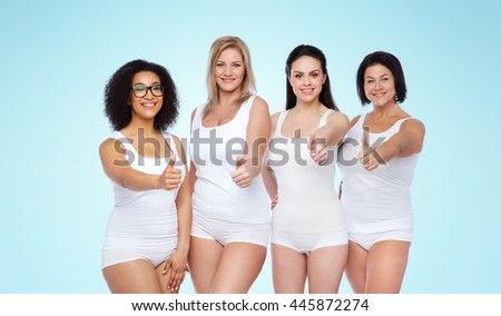 gesture, friendship, beauty, body positive and people concept - group of happy different women in white underwear showing thumbs up over blue background - stock photo