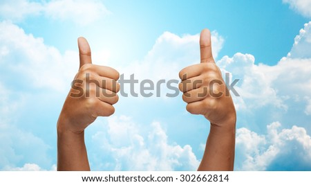 gesture, like, success, people and body parts concept - african woman hands showing thumbs up over blue sky and clouds background - stock photo