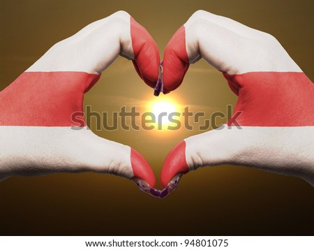 Gesture made by england flag colored hands showing symbol of heart and love during sunrise