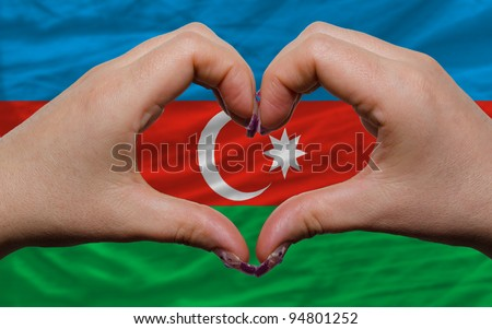 Gesture made by hands showing symbol of heart and love over national azerbaijan flag