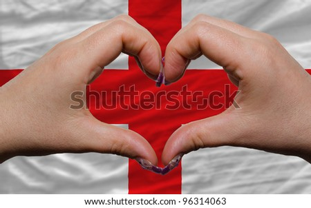 Gesture made by hands showing symbol of heart and love over national england flag