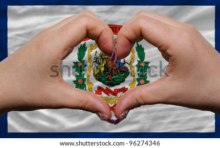 Gesture made by hands showing symbol of heart and love over us state flag of west virginia