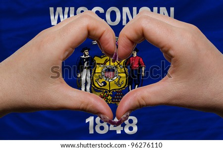 Gesture made by hands showing symbol of heart and love over us state flag of wisconsin - stock photo