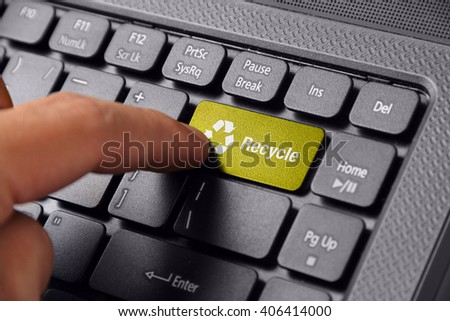 Gesture of a hand finger pushing the RECYCLE button on laptop - stock photo