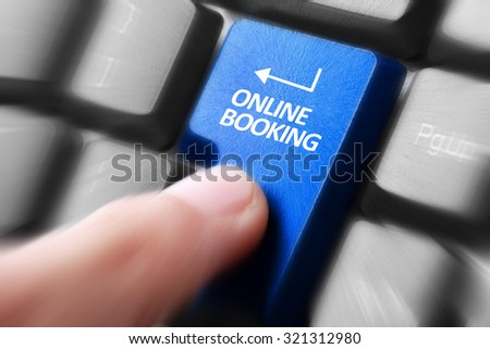 Gesture of finger pressing online booking button on a computer keyboard - stock photo