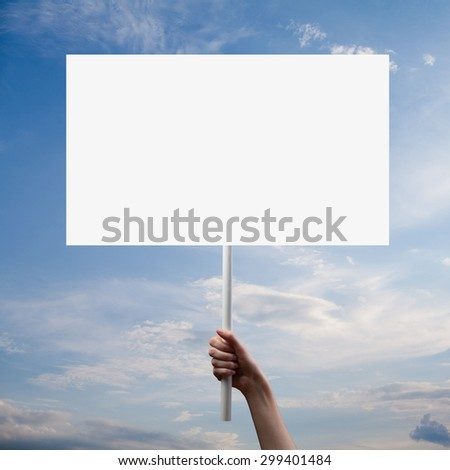gesture of hand holding a blank white paper isolated over dramatic dark sky background
