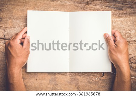 gesture of male's hand holding a book on old wooden table - stock photo