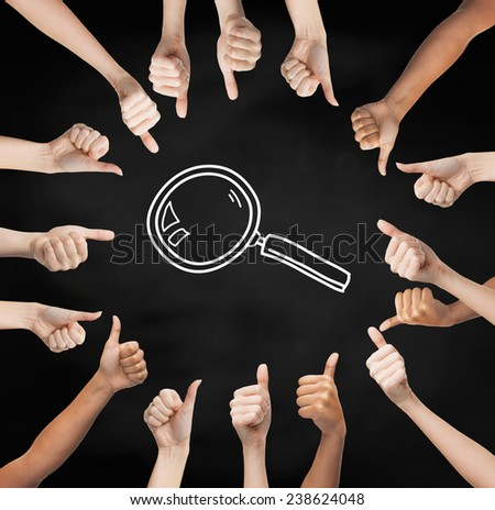 gesture, people and exploration concept - human hands showing thumbs up in circle over black board background with magnifier - stock photo