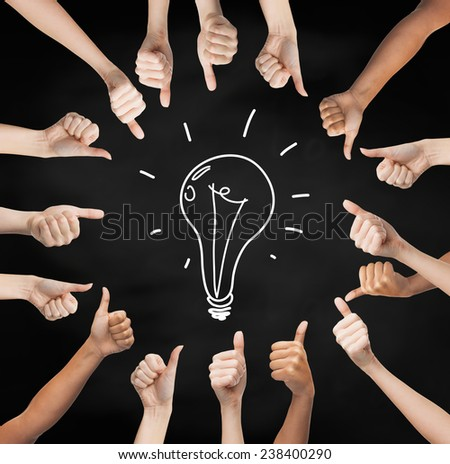gesture, people, idea and development concept - human hands showing thumbs up in circle over black board background with drawing of lightning bulb in center - stock photo