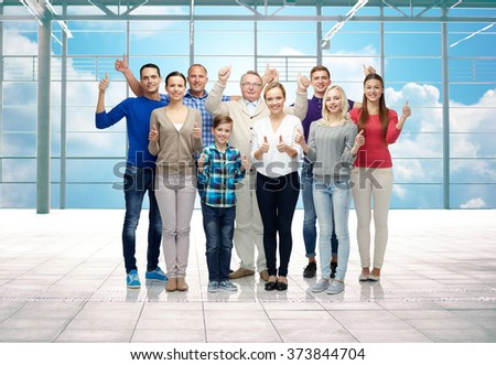 gesture, travel, vacation and people concept - group of happy people or big family showing thumbs up over airport terminal window and sky background - stock photo