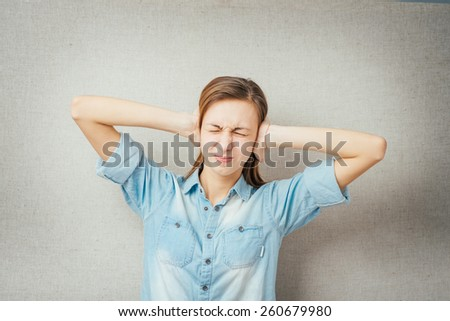 gesture woman covering her ears with his hands. isolated on gray background - stock photo