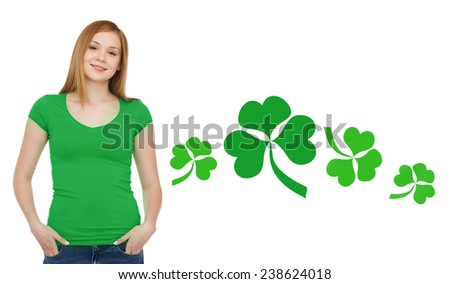 gestures, holidays, st. patricks day and people concept - happy teenager in blank green t-shirt over white background with shamrock or clover - stock photo