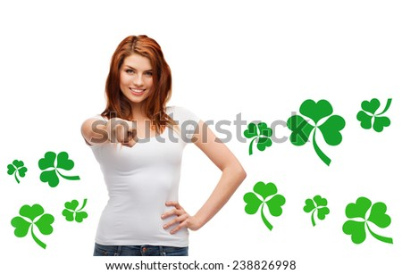 gestures, holidays, st. patricks day and people concept - happy teenager in blank white t-shirt pointing at you over white background with green shamrock or clover - stock photo