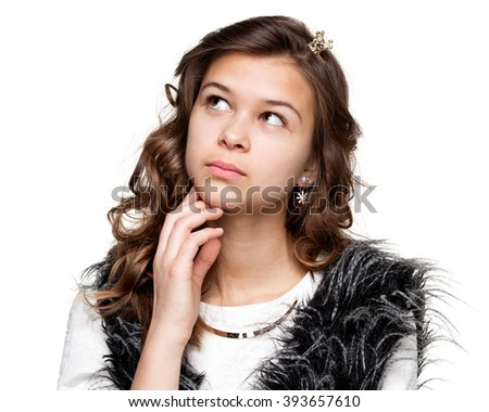 Gestures. Teenagers. Portrait of a young pensive girl in a light shirt and a fuzzy vest looking up, thinking, isolated on white background - stock photo