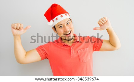 Gesturing asian man with Santa Claus hat. - stock photo