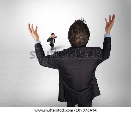 Gesturing businessman with tiny businessman against grey vignette