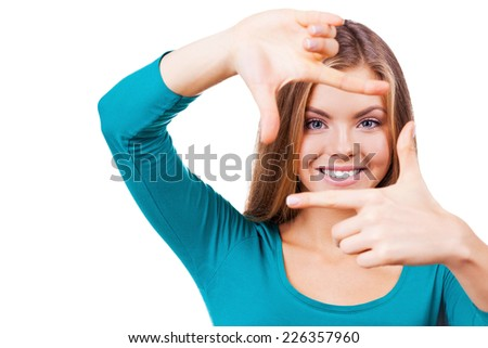 Gesturing finger frame. Beautiful young woman looking at camera and gesturing finger frame while standing isolated on white - stock photo