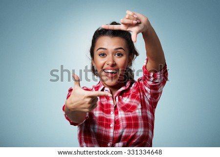 Gesturing finger frame. Portrait of handsome beautiful young mixed race woman looking at camera and gesturing finger frame while standing against isolated background - stock photo
