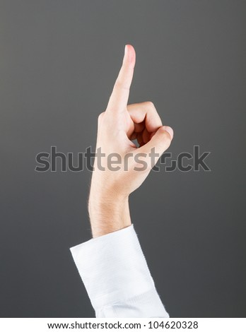 Gesturing hand grey blackboard background - stock photo