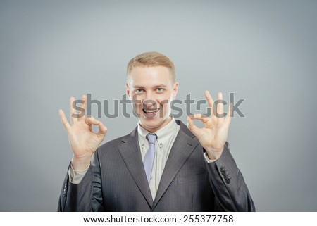 Gesturing OK sign. Cheerful young man in shirt and tie gesturing OK sign while standing against grey background - stock photo