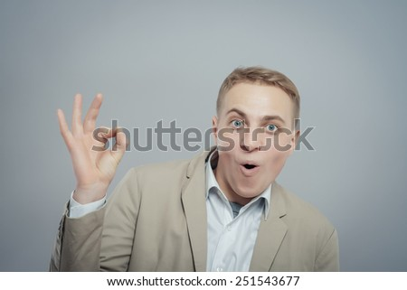 Gesturing OK sign. Cheerful young man in shirt gesturing OK sign while standing against grey background