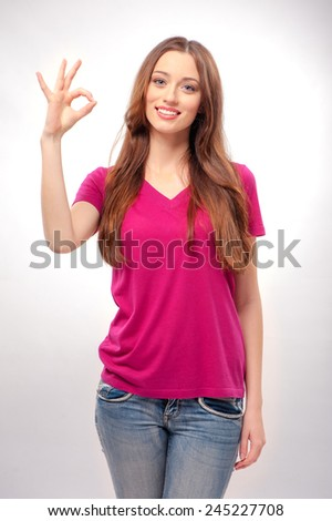 Gesturing OK sign. Half-length portrait of Happy young woman gesturing OK sign and smiling while standing on studio background - stock photo