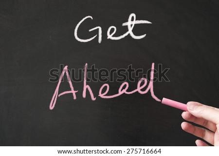 Get ahead words written on the blackboard using chalk - stock photo