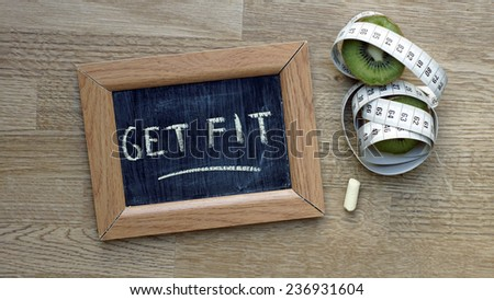 Get fit written on a chalkboard next to a kiwi an inches - stock photo