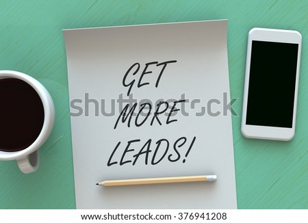 Get More Leads, message on paper, smart phone and coffee on table - stock photo