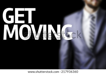 Get Moving written on a board with a business man on background - stock photo