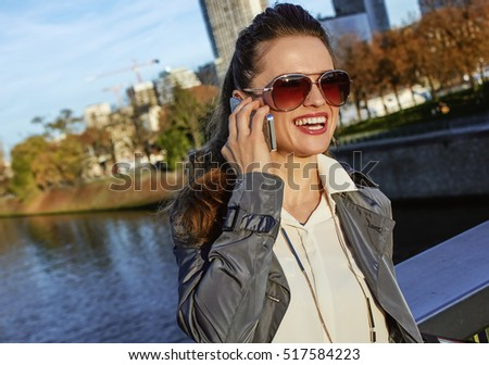Get your bags ready for the Paris autumn sales. smiling young fashion-monger in sunglasses talking on a smartphone near Eiffel tower