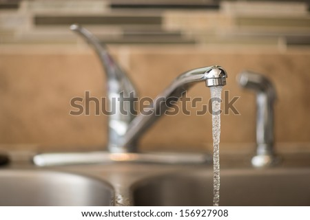 Getting a drink of water from the sink. View has shallow depth of field and is a head on view of a faucet - stock photo