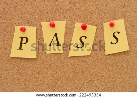 Getting a good grade, Four yellow notes on a cork board with the word Pass - stock photo