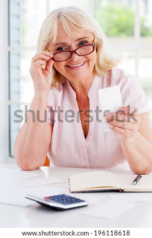 Getting her finances straight. Happy senior woman holding a bill and smiling at camera while sitting at the table