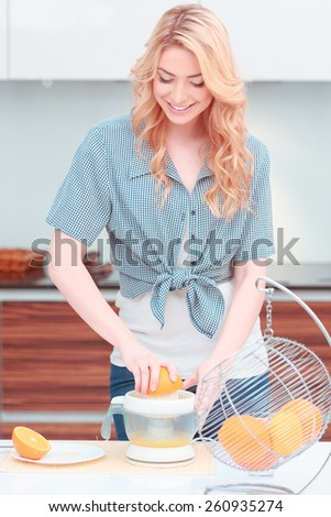 Getting her Vitamin C. Beautiful young woman making orange juice with juicer while standing against kitchen - stock photo