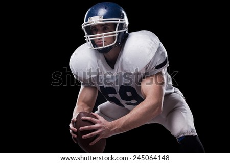 Getting ready to fight for this game.  American football player holding ball and looking away while standing against black background