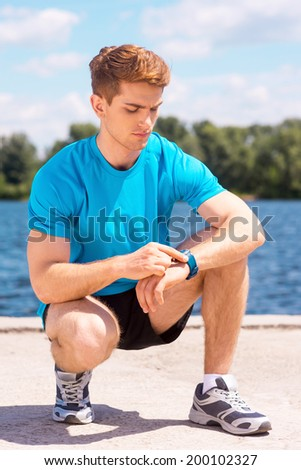 Getting ready to jogging. Handsome man checking time before jogging on riverbank