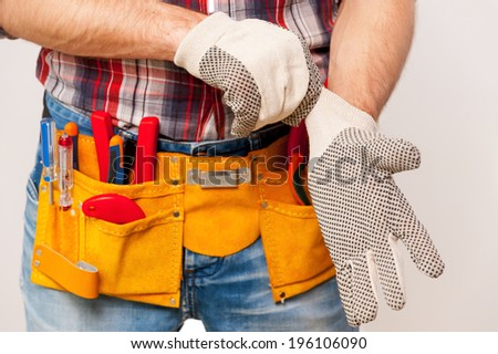 Getting ready to work. Close-up of handyman with tool belt wearing protective gloves while standing  against grey background - stock photo