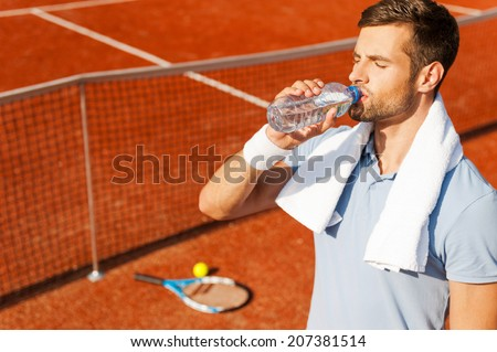 Getting refreshed after game. Thirsty young man in polo shirt and towel on shoulders drinking water while standing on tennis court  - stock photo
