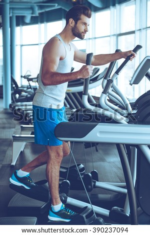 Getting the best body. Full length side view of young handsome man in sportswear looking away while working out on stepper at gym - stock photo