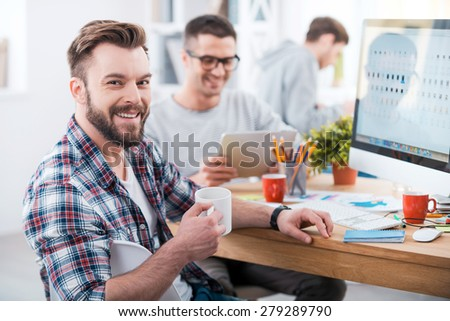 Getting the job done. Handsome young man holding a cup of coffee and smiling while sitting at desk in the office with his colleagues working in the background - stock photo